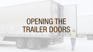 A truck driver opening trailer doors