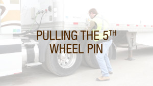 A truck driver pulling the fifth wheel pin