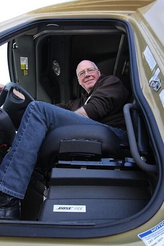 Truck driver sitting on bose ride system seat