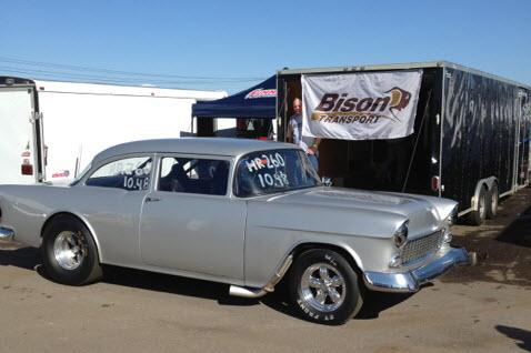 Drag racing car in front of Bison Transport flag